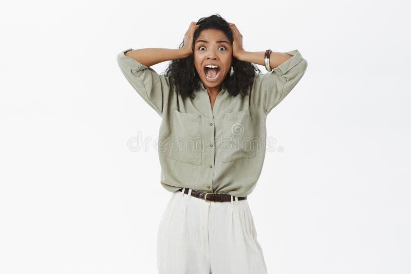 Retrato de asustado escena horrorosa que atestigua aturdida y chocada de la hembra afroamericana que grita de miedo foto de archivo
