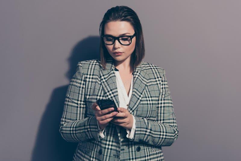 Retrato de atrativo celular de vista concentrado focalizado seguro com corte de cabelo do prumo ela seu usuário da senhora isolad fotografia de stock
