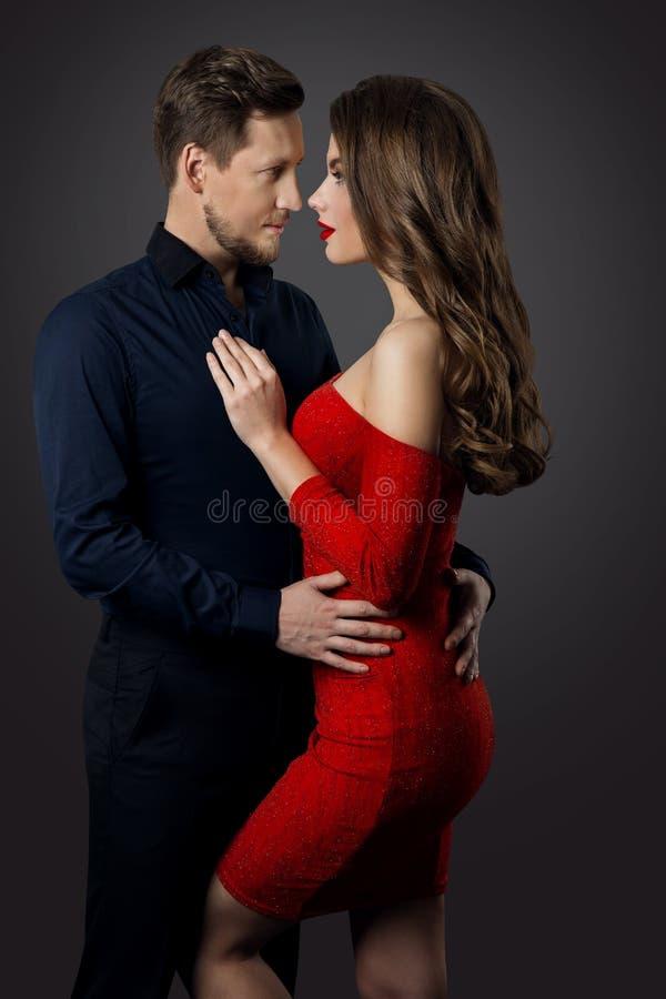 Retrato de beleza casal, linda mulher vestida de vermelho abraçando o homem legante, cara a cara fotografia de stock