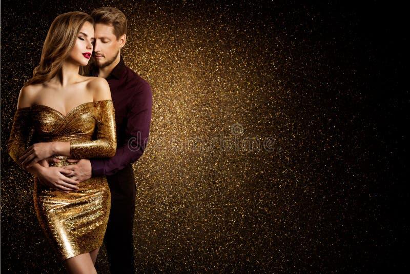 Retrato de beleza caseira, sonhando linda mulher em vestido dourado abraçando o homem elegante, amor imagem de stock royalty free