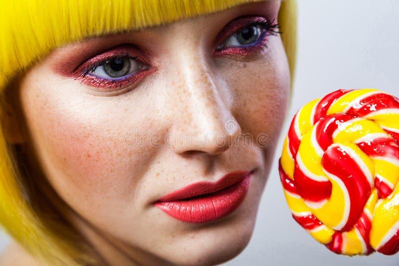 Retrato de beleza da calma e fofinha modelo feminina com sardas, maquiagem vermelha e peruca amarela, segurando um doce colorido n foto de stock
