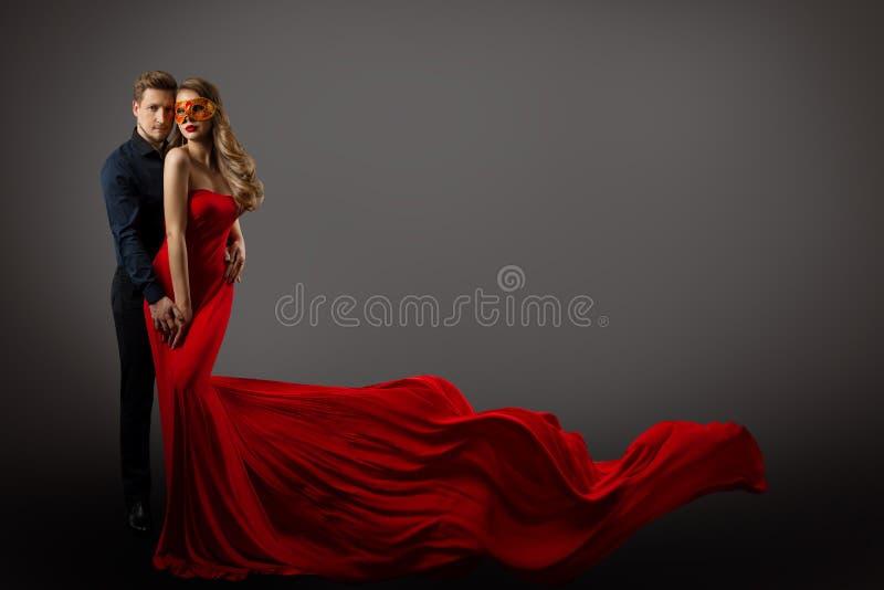 Retrato de belleza pareja, mujer hermosa en máscara y vestido rojo y hombre elegante, vestido con flúor fotografía de archivo libre de regalías