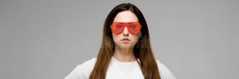 Retrato de bem sucedido bonito emocional mais o modelo do tamanho nos óculos de sol que estão no estúdio que olha in camera de le imagem de stock royalty free