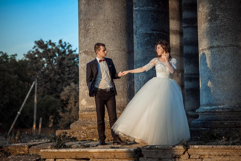 Retrato de boda al aire libre romántico de los pares magníficos del recién casado que llevan a cabo las manos mientras que se col imagen de archivo