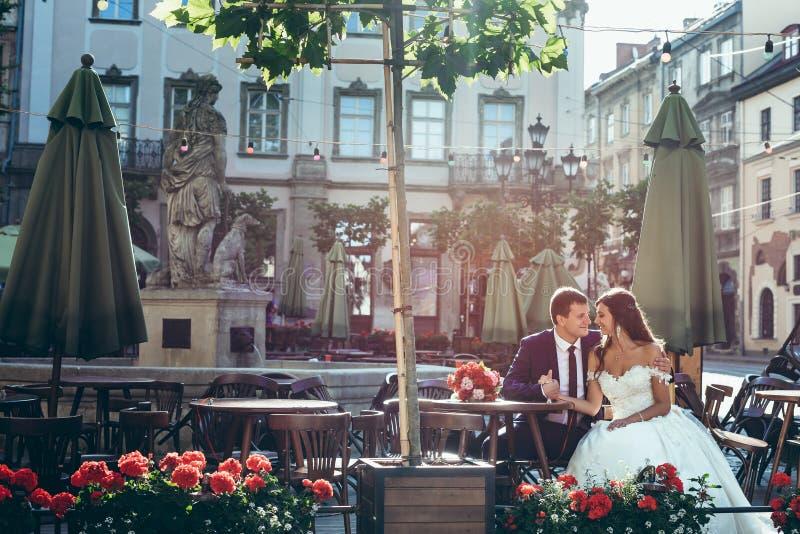 Retrato de boda romántico Apenas pareja casada atractiva feliz si que lleva a cabo las manos y que abraza mientras que se sienta  fotografía de archivo