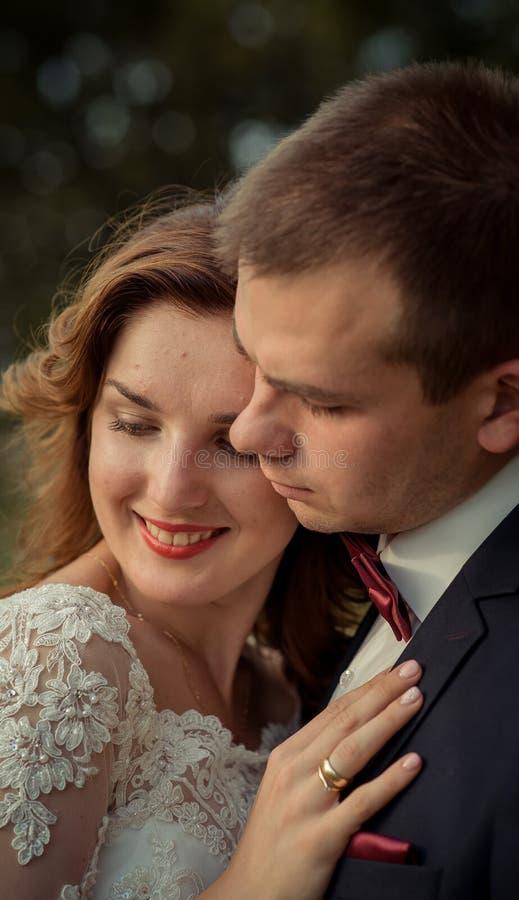Retrato de boda sensible del primer de los recienes casados sonrientes bonitos que abrazan suavemente imagenes de archivo