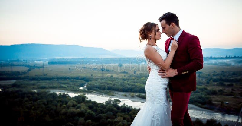 Retrato de boda sensible de los pares lindos del recién casado Fondo del paisaje magnífico durante la puesta del sol foto de archivo libre de regalías