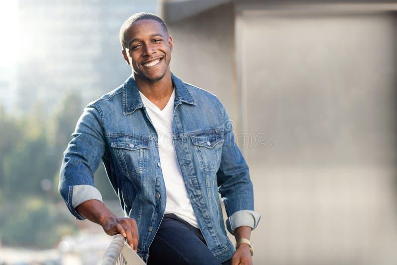 Retrato de cabeça de estilo de vida de um homem africano americano em um casaco jean azul em um terraço urbano, belo sorriso imagens de stock royalty free