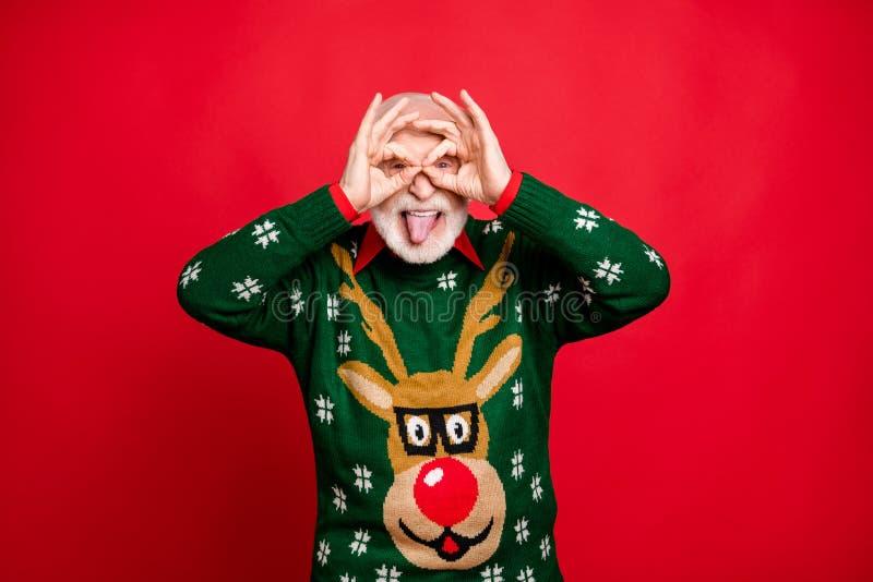 Retrato de cabelos grisalhos divertidos e engraçados desfrutam da festa de Natal faz binóculos com seus dedos imaginem que ele es fotografia de stock