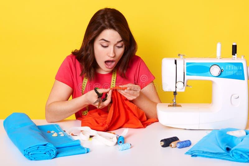 Retrato de chica atelier en taller de costura, mujer sostiene tijeras y trozos de tela roja en las manos, se sienta con asombro foto de archivo