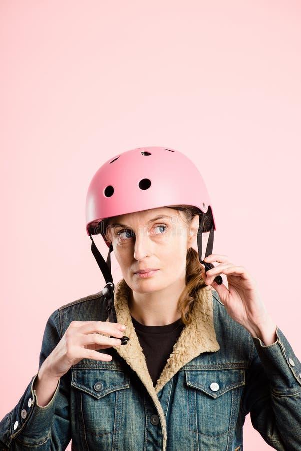 Fundo de ciclagem vestindo do rosa do retrato do capacete da mulher engraçada real fotografia de stock royalty free