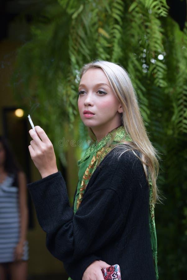 Retrato de cigarros de fumo de uma jovem mulher bonita fotos de stock royalty free