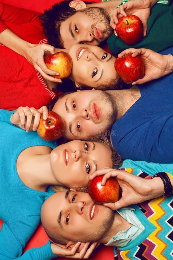 Retrato de cinco amigos próximos à moda que abraçam e que encontram-se sobre o re foto de stock royalty free