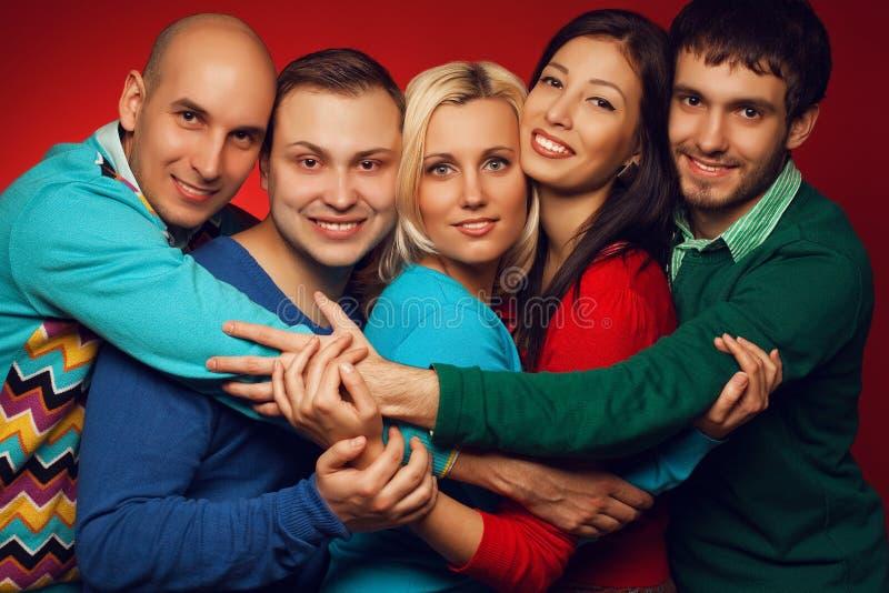Retrato de cinco amigos próximos à moda que abraçam, sorrindo e posi imagens de stock