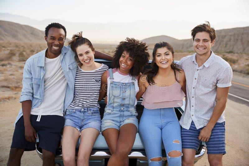 Retrato de cinco amigos que sentam-se no tronco do carro clássico na viagem por estrada imagem de stock royalty free