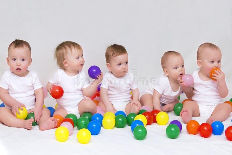 Retrato de cinco bebés lindos en el fondo ligero que juega con las bolas coloridas imagenes de archivo