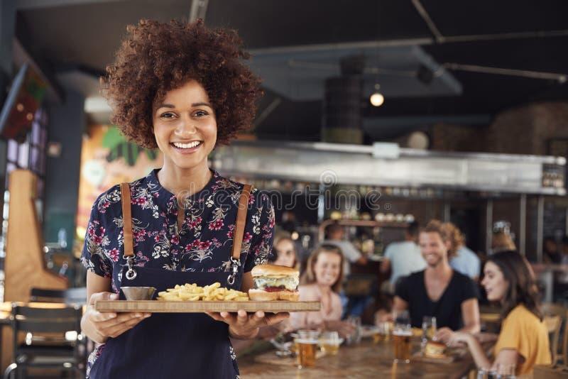 Retrato de clientes de Serving Food To da empregada de mesa no restaurante ocupado da barra fotografia de stock