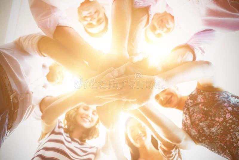 Retrato de colegas de sorriso do negócio com suas mãos empilhadas fotos de stock