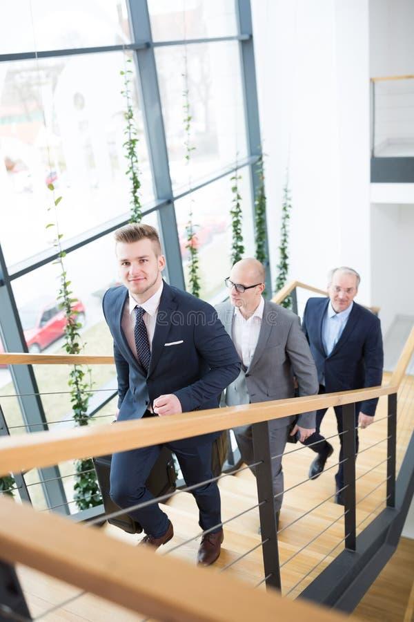 Retrato de colegas de Moving Upstairs With do homem de negócios em Offic imagens de stock royalty free