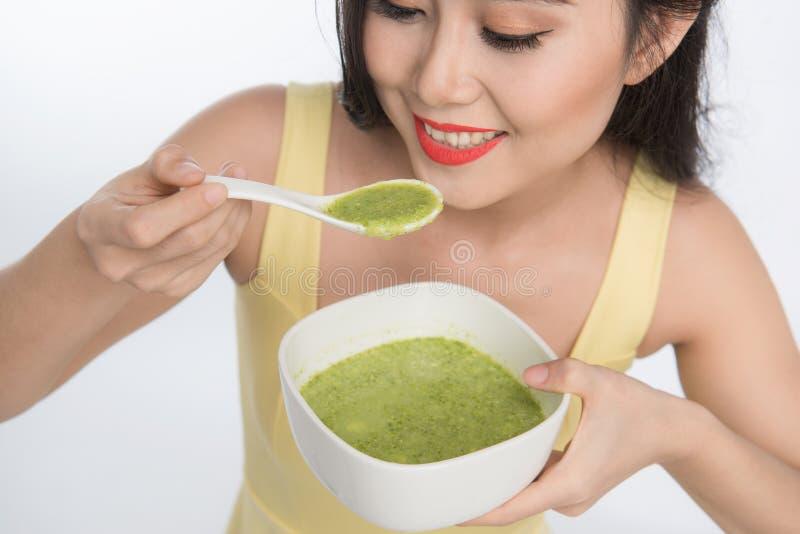 Retrato de comer asiático da mulher/que guarda uma placa do vegetabl verde imagens de stock royalty free