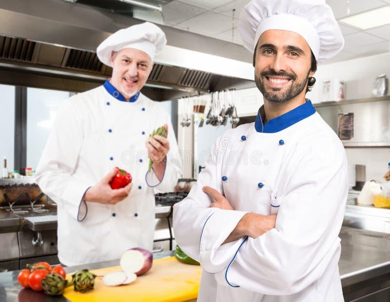 Retrato de cozinheiros chefe de sorriso em uma cozinha imagens de stock