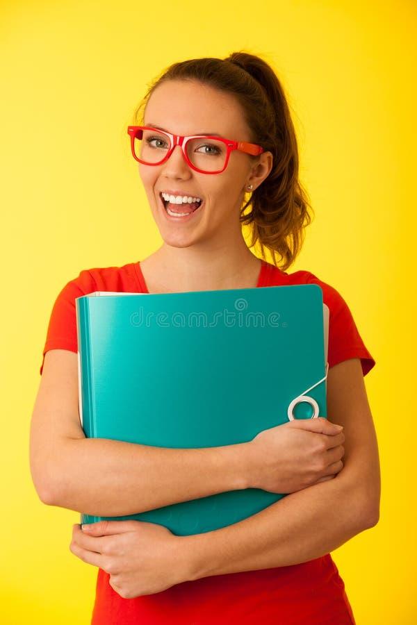 Retrato de Creaqtive de uma mulher feliz caucasiano nova bonita no t-shirt vermelho com monóculos vermelhos fotografia de stock royalty free