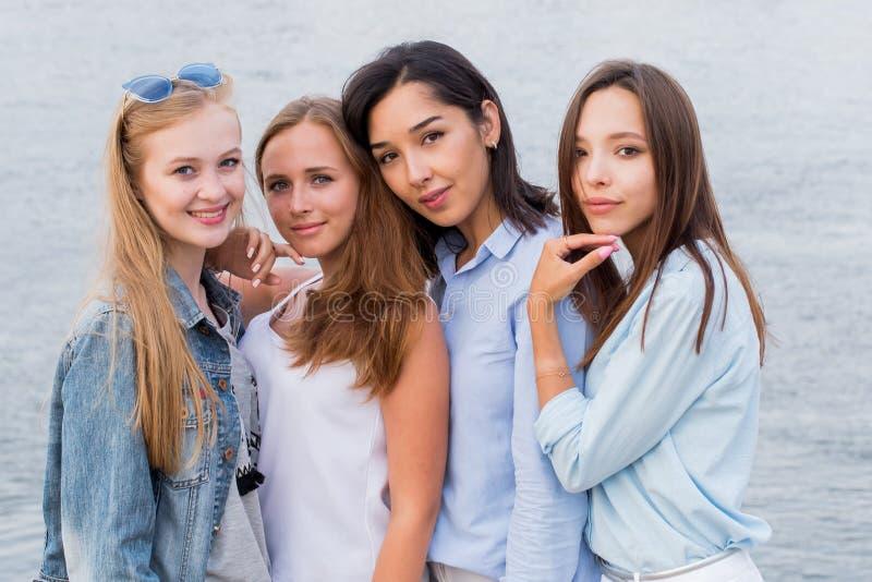 Retrato de cuatro amigos femeninos jovenes que caminan en la orilla de mar que mira la risa de la cámara imagenes de archivo