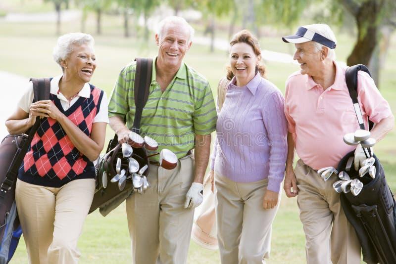 Retrato de cuatro amigos que disfrutan de un golf del juego imágenes de archivo libres de regalías