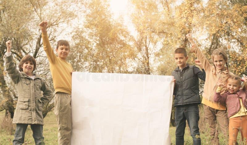 Retrato de cuatro niños en el parque Niños felices que gozan en a imagenes de archivo