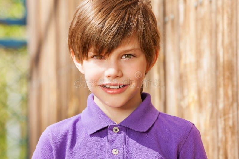 Retrato de dez anos de menino idoso no polo roxo imagens de stock royalty free