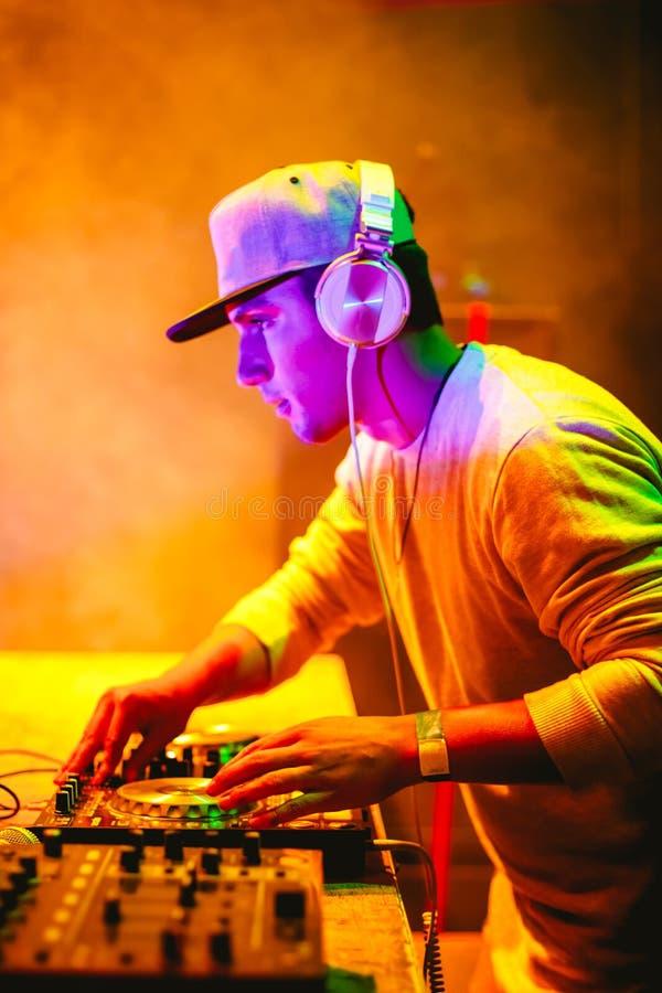 Retrato de DJ joven que juega música de mezcla en el partido de la noche bajo luces coloridas fotografía de archivo
