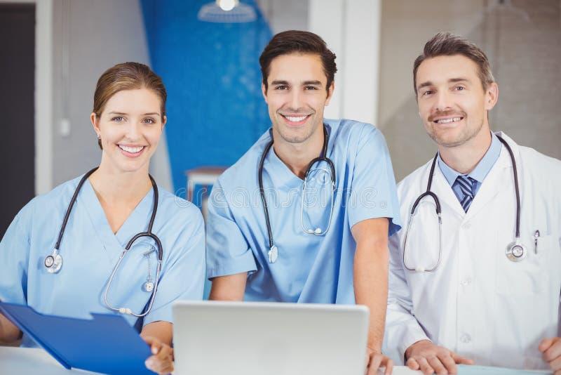 Retrato de doctores alegres con el ordenador portátil y el tablero imagenes de archivo