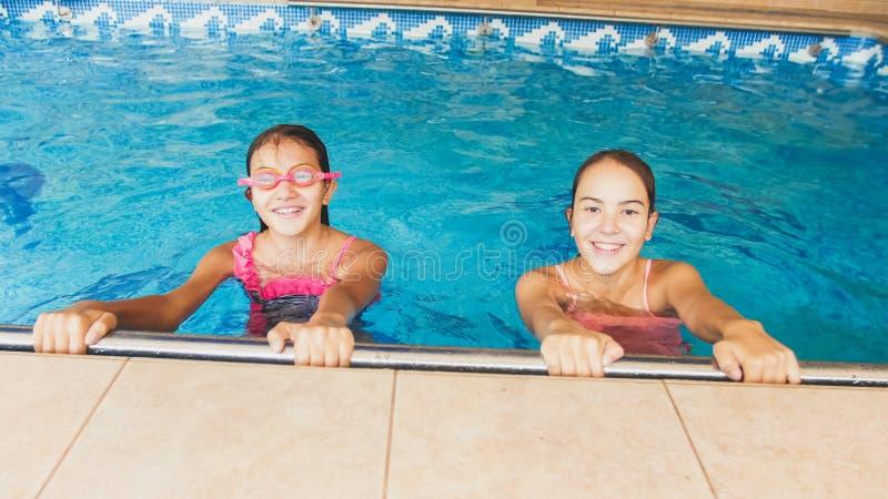 Retrato de dois adolescentes de sorriso na nata??o na associa??o Fam?lia que tem o divertimento e que relaxa na ?gua em f?rias de foto de stock