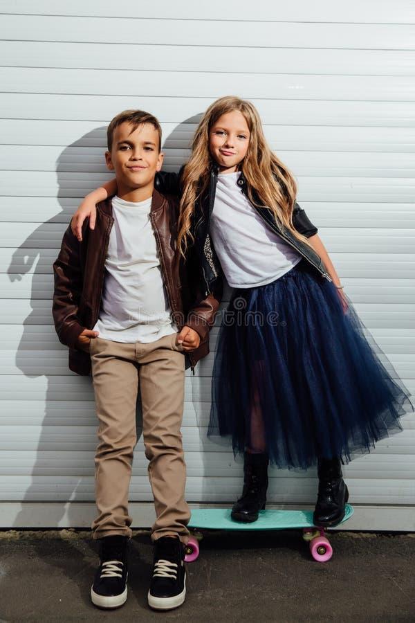 Retrato de dois alunos adolescentes em um fundo da porta da garagem em uma rua do parque da cidade foto de stock royalty free