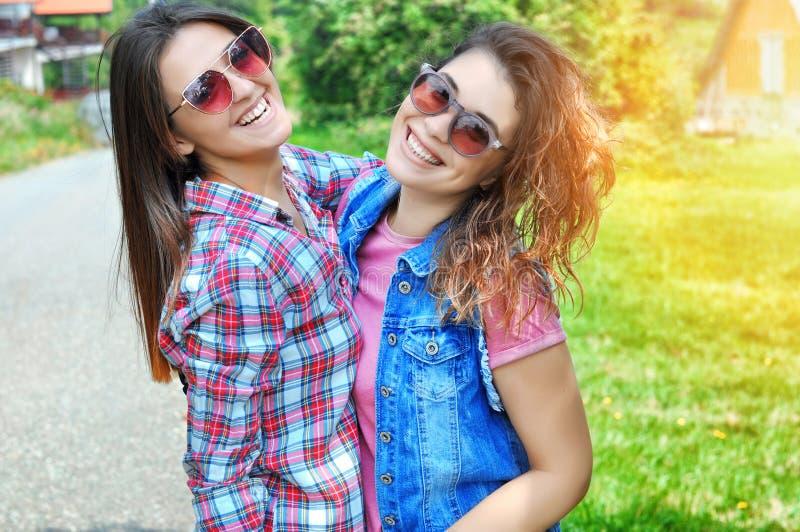 Retrato de dois amigos fêmeas de riso que vestem os óculos de sol que olham a câmera imagens de stock