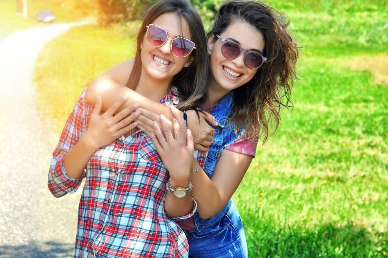 Retrato de dois amigos fêmeas de riso que vestem os óculos de sol que olham a câmera fotos de stock
