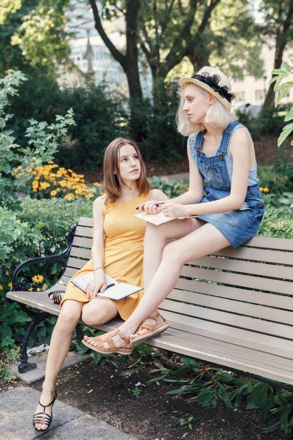 Retrato de dois amigos unformal caucasianos brancos dos adolescentes dos estudantes do moderno das moças fora no parque fotos de stock royalty free