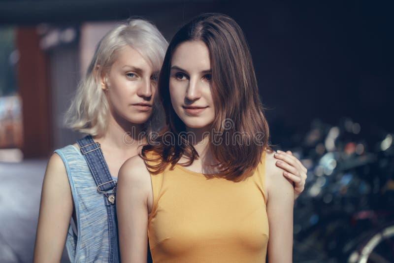 Retrato de dois amigos unformal caucasianos brancos dos estudantes do moderno das moças fora no aperto do dia de verão imagem de stock
