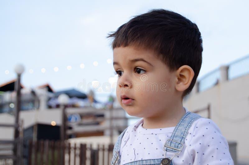 Retrato de dois anos bonitos da obscuridade velha do menino para ouvir-se imagens de stock