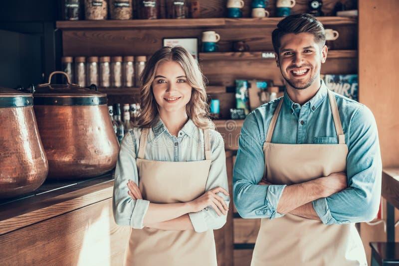 Retrato de dois baristas nos aventais na cafetaria imagens de stock