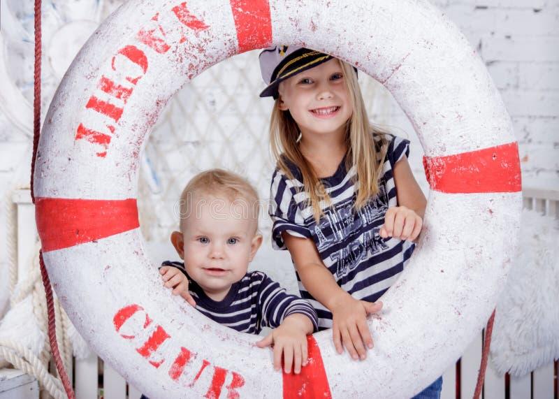 Retrato de dois bonitos e meninas europeias impertinentes na roupa dos marinheiros fotografia de stock