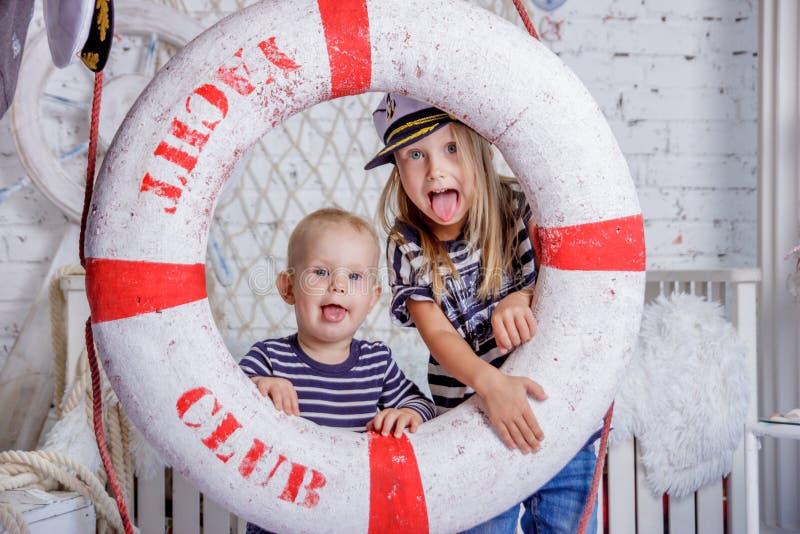 Retrato de dois bonitos e meninas europeias impertinentes na roupa dos marinheiros fotos de stock