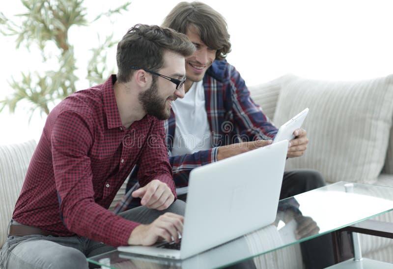 Retrato de dois desenhistas da Web que discutem um projeto na frente de um portátil imagens de stock