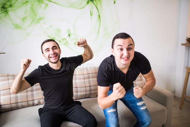 Retrato de dois fãs de futebol entusiasmado que olham a tevê no sofá imagem de stock