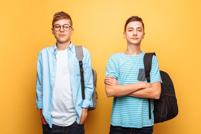 Retrato de dois indivíduos à moda felizes, adolescentes, isolados no fundo amarelo imagens de stock