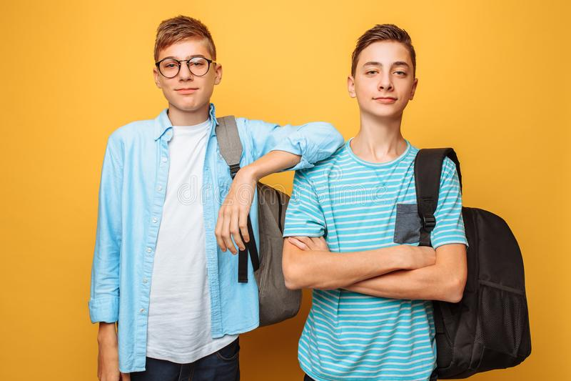 Retrato de dois indivíduos à moda felizes, adolescentes, isolados no fundo amarelo imagens de stock royalty free
