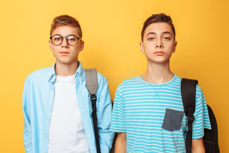 Retrato de dois indivíduos à moda felizes, adolescentes, isolados no fundo amarelo fotos de stock royalty free