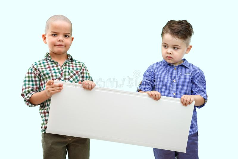 Retrato de dois meninos que guardam o sinal branco no fundo isolado foto de stock royalty free
