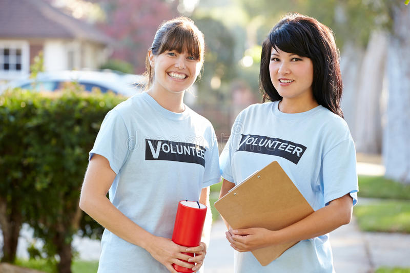 Retrato de dois voluntários da caridade da fêmea na rua fotografia de stock