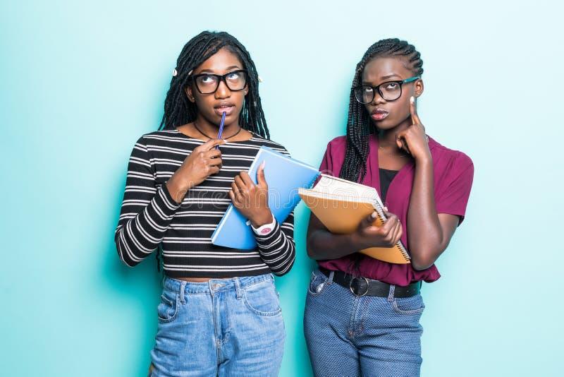 Retrato de dos adolescentes jovenes africanos de la escuela que sostienen cuadernos y que miran la cámara sobre fondo verde foto de archivo libre de regalías